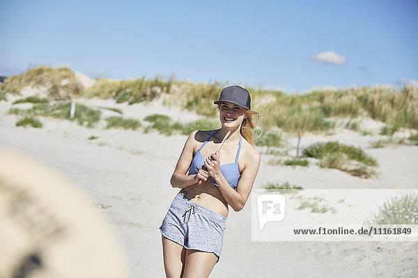 Fröhliche junge Frau am Strand beim Strandpaddeln