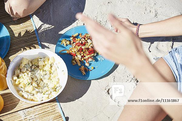 Zwei Freunde am Strand bei einem Salat.