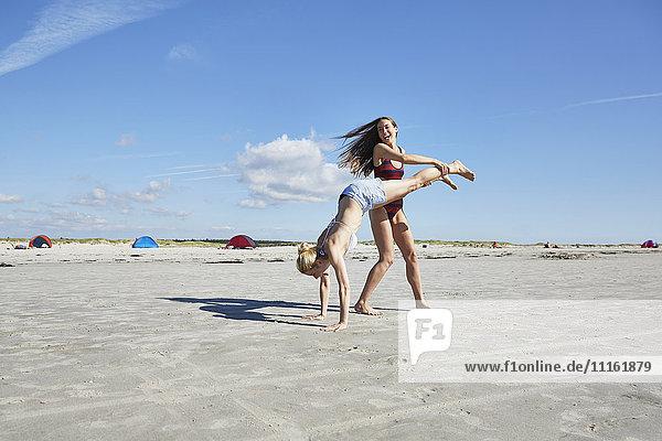 Junge Frau hilft Freundin beim Handstand am Strand