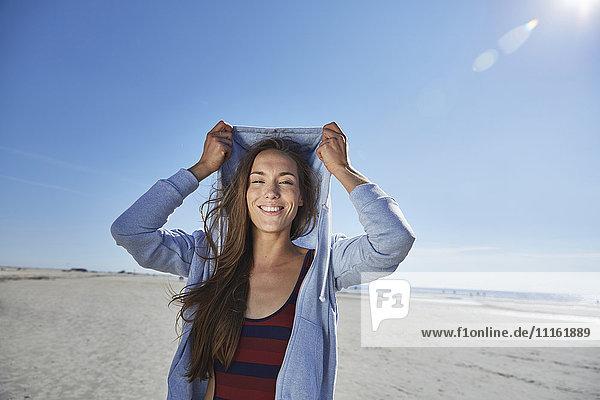 Lächelnde junge Frau mit Kapuze am Strand