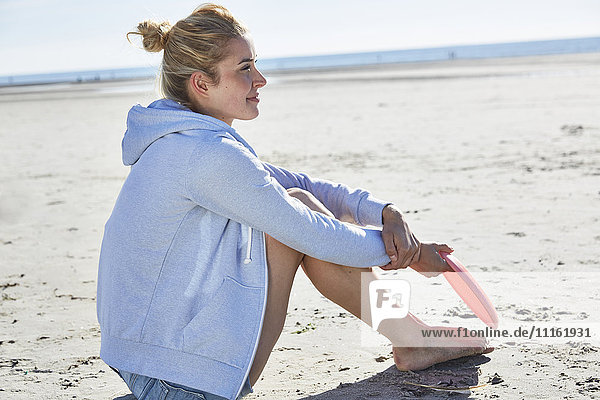 Junge Frau mit Kapuze am Strand sitzend