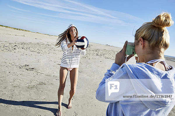Frau fotografiert Freundin mit Beachvolleyball am Strand