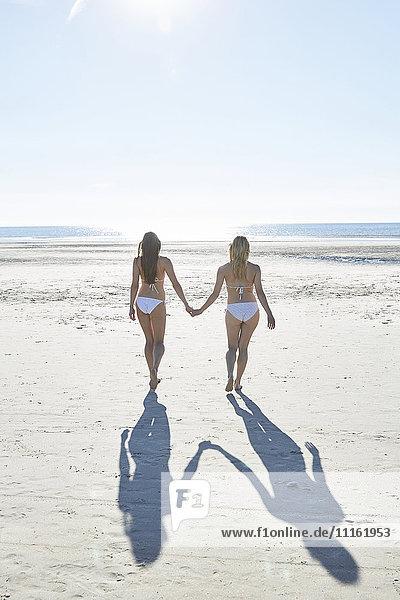 Zwei Freundinnen im Bikini gehen Hand in Hand am Strand.