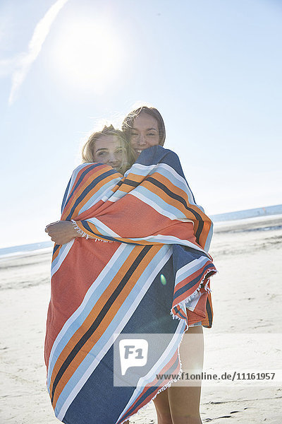 Two young women wrapped in a blanket on the beach