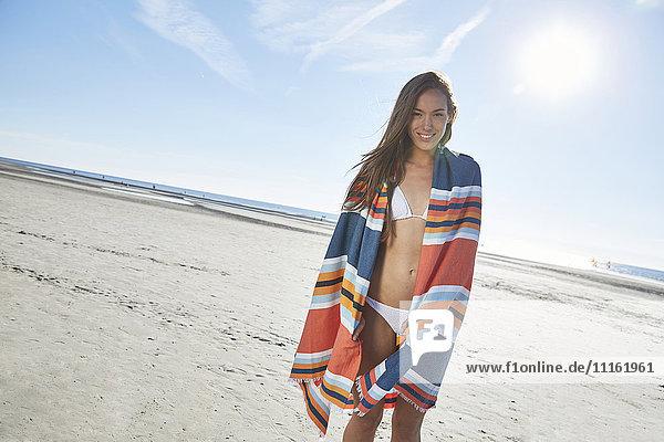 Lächelnde junge Frau im Bikini mit Decke am Strand