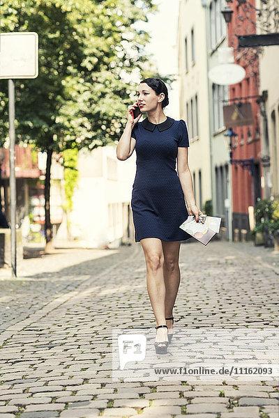 Junge Frau am Handy zu Fuß in der Stadt