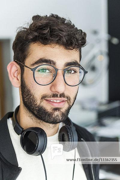 Porträt eines lächelnden Mannes mit Brille und Kopfhörer