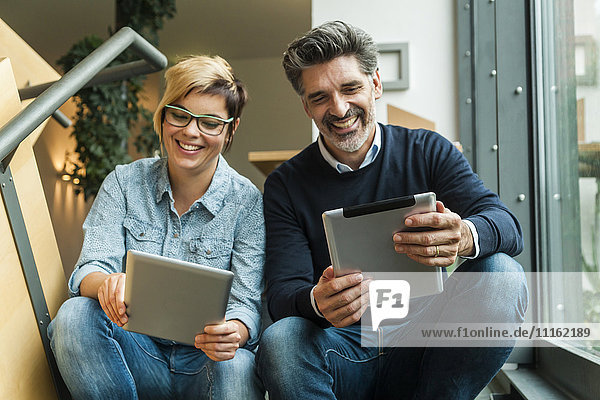 Businesman and woman sitting on stairs  using digital tablets