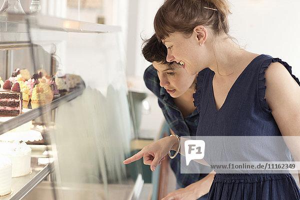 Zwei Freunde  die in einem Coffee-Shop Gebäck aussuchen.