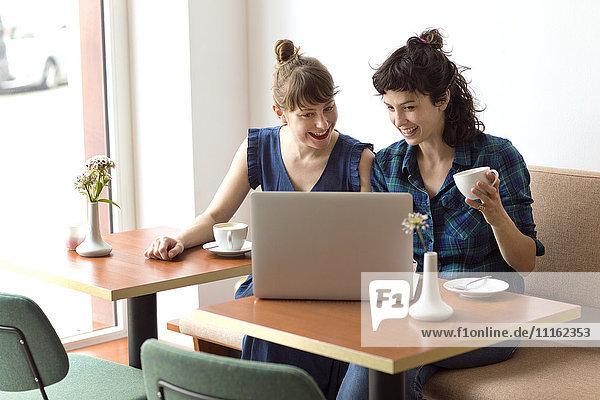 Zwei lächelnde Freunde  die in einem Café sitzen und auf den Laptop schauen.