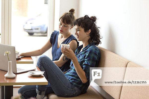 Zwei Freunde sitzen in einem Café und schauen sich den Laptop an.