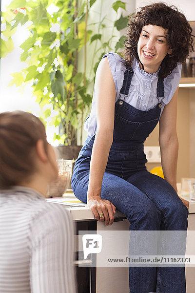 Zwei Freundinnen kommunizieren in der Küche