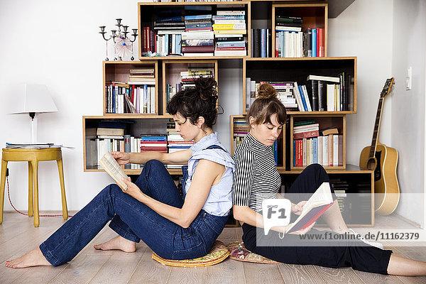 Zwei Lesefreunde sitzen Rücken an Rücken auf dem Boden des Wohnzimmers.
