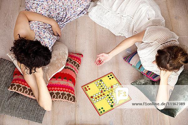 Draufsicht von zwei besten Freunden  die zu Hause auf dem Boden liegen und Ludo spielen.