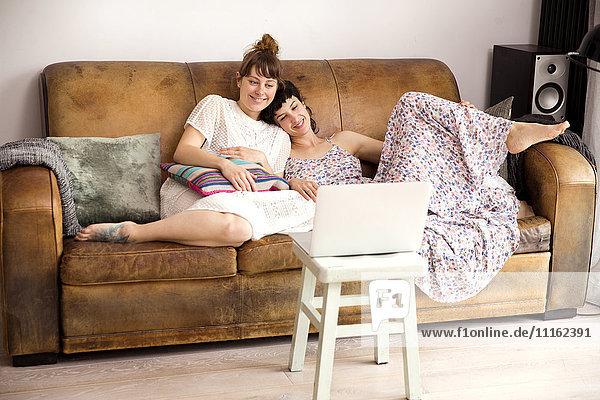 Zwei Freunde auf der Ledercouch sehen sich einen Film auf dem Laptop an
