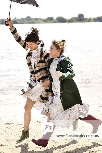 Zwei Freunde laufen Seite an Seite am Strand mit einem Regenschirm.