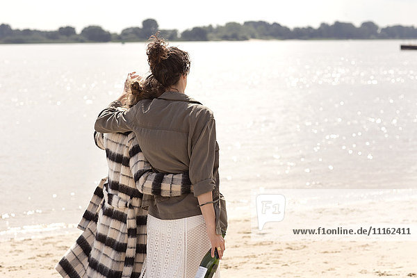 Back view of two friends walking arm in arm on the beach with bottle of sparkling wine