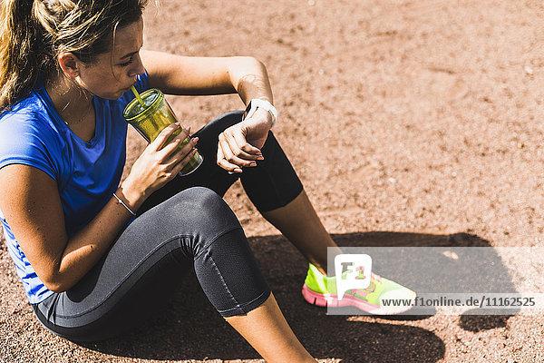 Sportliche junge Frau sitzt auf dem Sportplatz und trinkt aus der Tasse und schaut auf smartwatch.