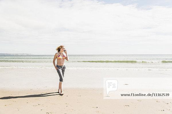 Teenager-Mädchen am Handy am Strand spazieren gehen