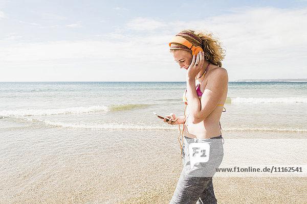 Teenagermädchen beim Musikhören am Strand