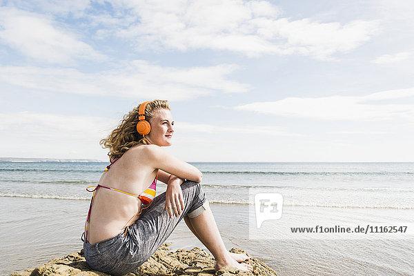 Teenager-Mädchen sitzt auf einem Felsen am Strand und hört Musik.