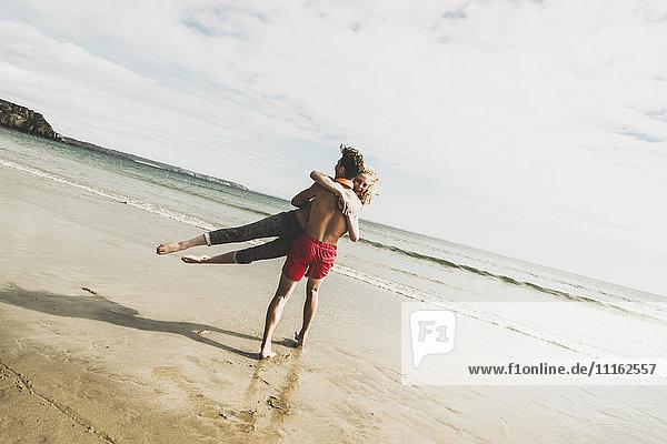 Verspieltes Teenager-Pärchen am Strand