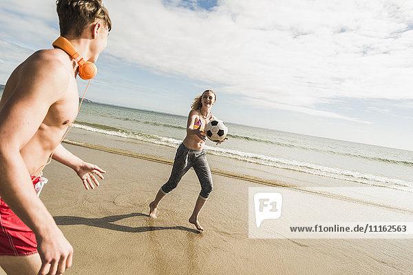 Teenager-Mädchen und junger Mann spielen mit einem Ball am Strand