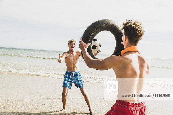 Zwei Freunde  die mit Ball und Reifen am Strand spielen.