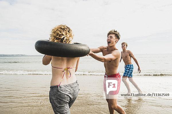 Freunde haben Spaß mit einem Reifen am Strand