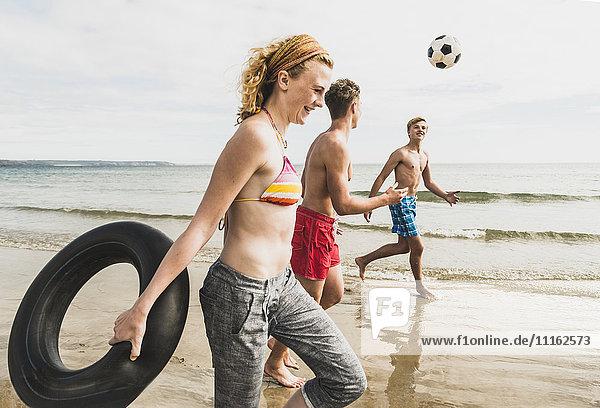 Freunde  die mit Ball und Reifen am Strand spazieren gehen.