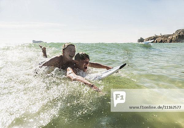 Zwei Freunde haben Spaß auf dem Surfbrett im Meer