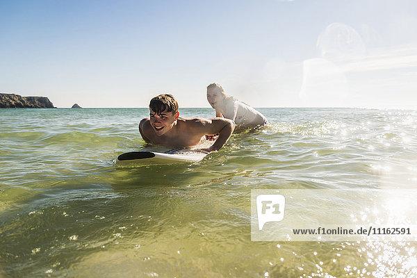 Teenagerpaar auf dem Surfbrett im Meer