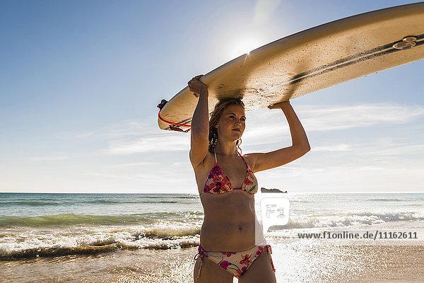 Teenager Mädchen mit Surfbrett am Meer