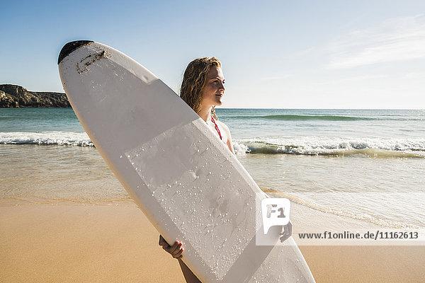 Teenagermädchen mit Surfbrett am Meer