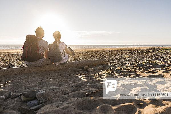 Frankreich  Bretagne  Finistere  Halbinsel Crozon  Paar beim Strandspaziergang  am Strand sitzen  Sonnenuntergang genießen
