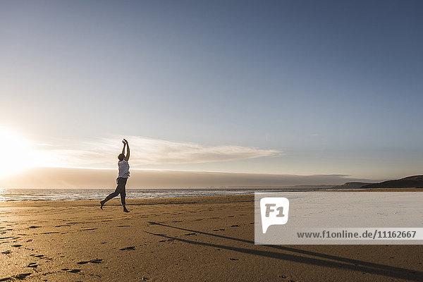 Frankreich  Bretagne  Halbinsel Crozon  Frau beim Springen am Strand bei Sonnenuntergang