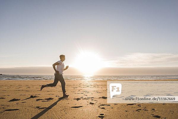 Frankreich  Bretagne  Halbinsel Crozon  Frau läuft am Strand bei Sonnenuntergang