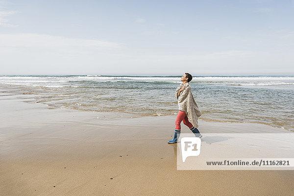 Reife Frau  die am Strand spazieren geht.