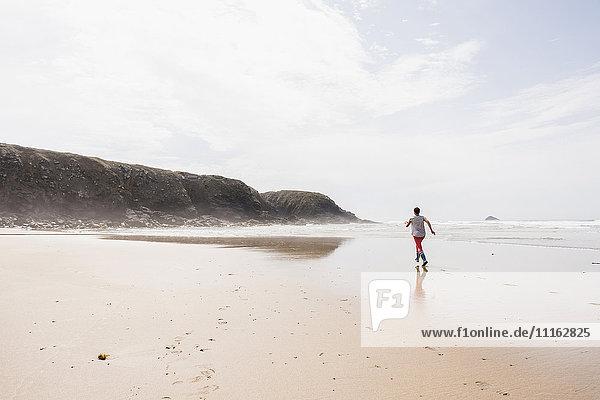 Reife Frau  die am Strand rennt.