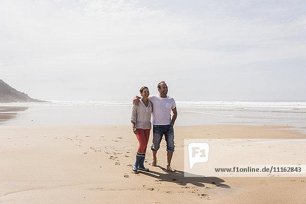 Ein reifes Paar  das am Strand spazieren geht.