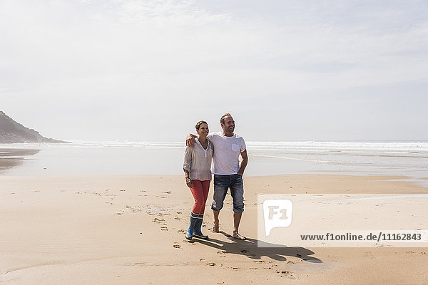 Mature couple walking on the beach