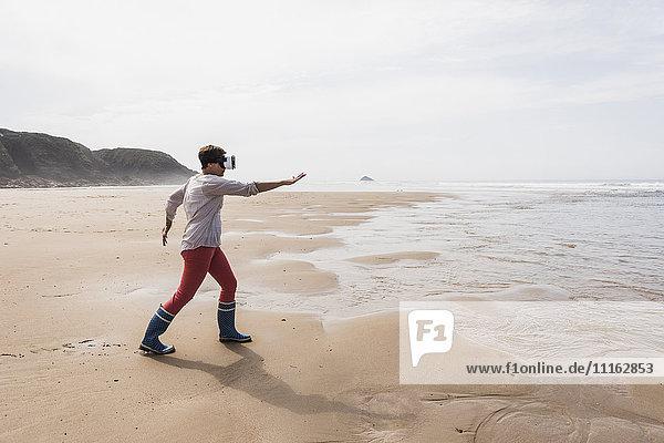 Reife Frau am Strand mit VR-Brille