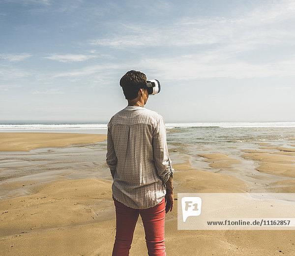 Reife Frau am Strand stehend mit VR-Brille