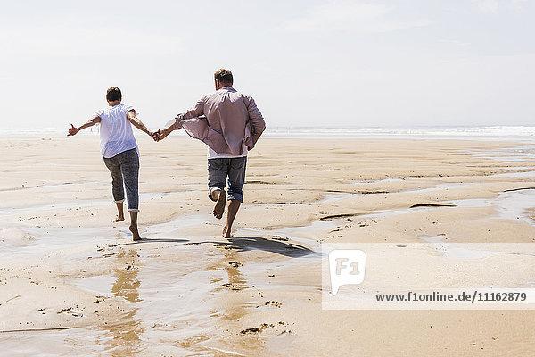 Ein reifes Paar  das am Strand rennt.