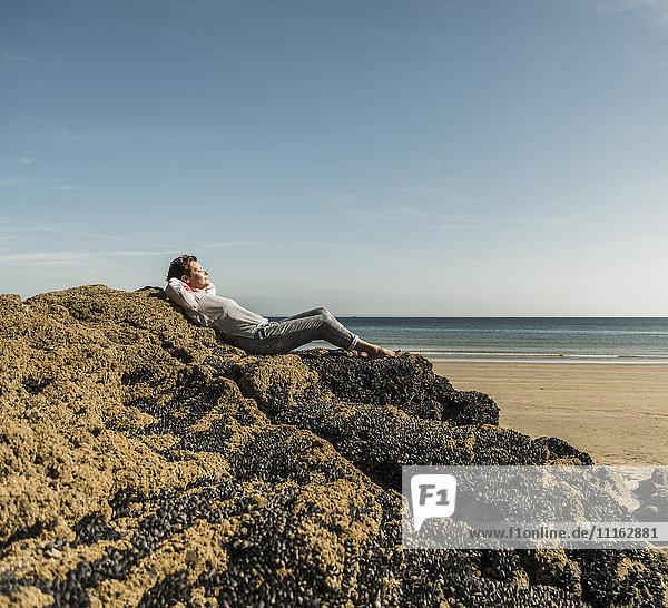 Reife Frau entspannt sich am Strand auf dem Felsen