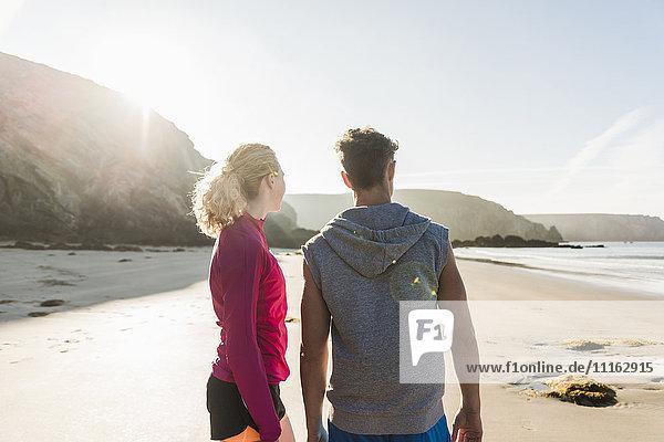 Frankreich  Halbinsel Crozon  sportliches junges Paar am Strand stehend