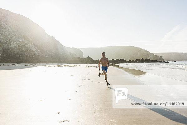 Frankreich  Halbinsel Crozon  junger Mann  der am Strand läuft