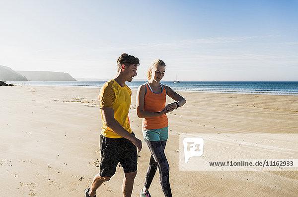 Frankreich  Halbinsel Crozon  sportliches junges Paar beim Spaziergang am Strand