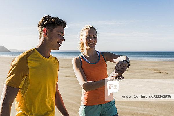Frankreich  Halbinsel Crozon  sportliches junges Paar am Strand mit Blick auf die Uhr