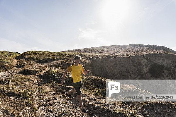 Frankreich  Halbinsel Crozon  junger Mann  der an der Küste läuft